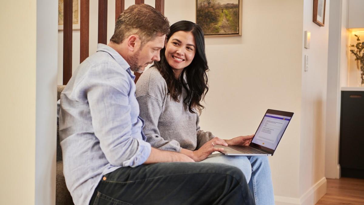 Muž a žena provádí výběr půjčky na notebooku.